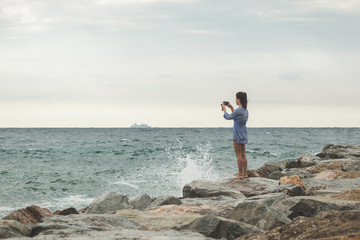 young woman taking photos of a ship in the ocean on her smartphone. travel smartphonography