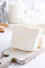 Fresh cottage cheese on rustic white wooden board