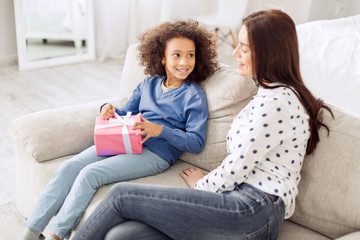 Congratulations. Attractive content curly-haired girl smiling and holding her gift while looking at her mother sitting near her