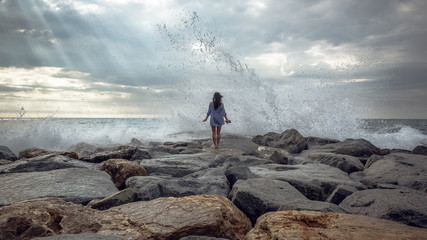 young woman standing on stones while big wave hitting shore