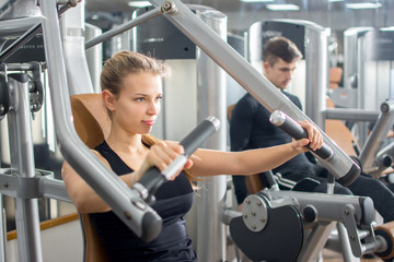 Sporty blonde girl workout on exercise machine in gym.
