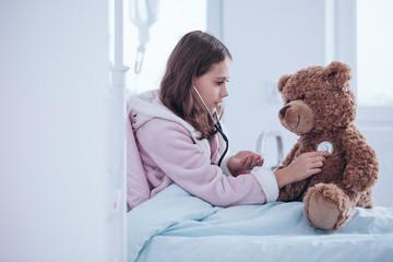 Girl examining teddy bear