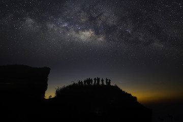 The milky way galaxy stars on the mountain and silhouette of tourists photographer. Phu Chi fa National Park. Chiang Rai Thailand