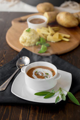 Vegetable cream soup with shrimps and croutons in white bowl close up