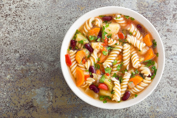 Minestrone soup. Vegetable soup with fresh tomato, celery, carrot, zucchini, onion, pepper, beans and pasta. Dish of italian cuisine.
