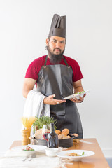 Handsome bearded cheef cook prepairing spaghetti on a kitchen, Chef cooks meal
