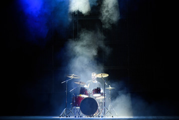 music, people, musical instruments and entertainment concept - male musician with drumsticks playing drums on the stage.
