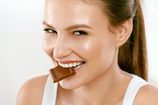Woman Eating Chocolate. Beautiful Girl With Sweets.