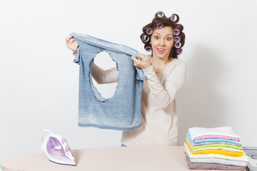 Shocked fun crazy housewife, curlers on hair in light clothes holding burned shirt with hole made by iron, standing at ironing board. Woman isolated on white background. Copy space for advertisement.
