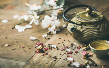 Traditional Asian tea ceremony arrangement. Iron teapot, cups, blooming almond flowers, dried rose buds and candles over wooden table background, selective focus, copy space