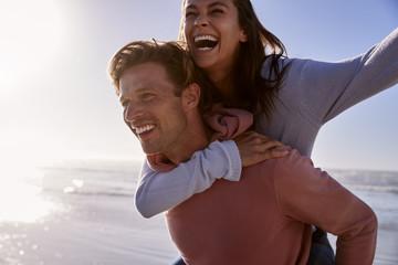 Man Giving Woman Piggyback On Winter Beach Vacation