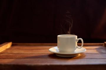 Чашка кофе на деревянном коричневом фоне в лучах солнца