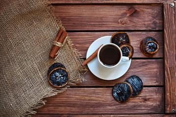 Чашка кофе с салфеткой из мешковины, сушеными дольками лимона и палочками корицы на деревянном коричневом фоне