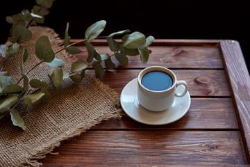 Чашка кофе с дымком, ветками эвкалипта, салфеткой из мешковины на деревянном коричневом фоне