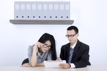 Businesspeople discussing with tablet computer