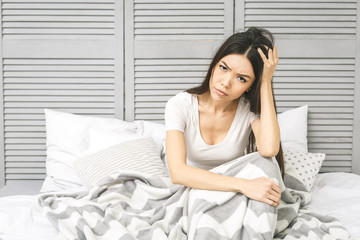 Woman Suffering From Depression Sitting On Bed In Pajamas