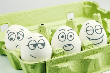 Four eggs in eggbox. Types of temperaments. Sanguine, choleric, phlegmatic and melancholic.