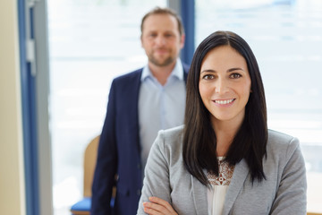 Portrait of businesswoman with man in background