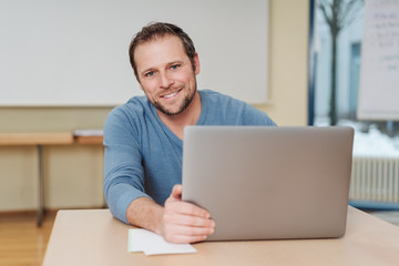 Cheerful man sitting in front of computer