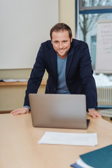 Smiling man standing over desk with laptop