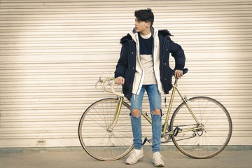 young to the fashion with the bicycle in the street of the city