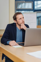 Businessman sitting at a desk deep in thought