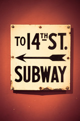 New York City subway entrance sign against wall