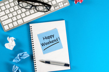 Happy Weekend message in notebook on office desk with empty space for text, mockup or template