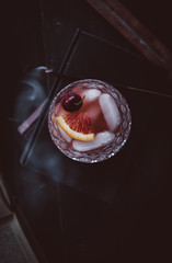 Cocktail with ice cubes, orange slice and cherry