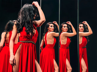 Portrait of beautiful brunette woman in red shoes and dress standing near the mirrors
