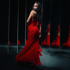 Portrait of beautiful brunette woman in red shoes and dress turning around and dancing near the mirrors