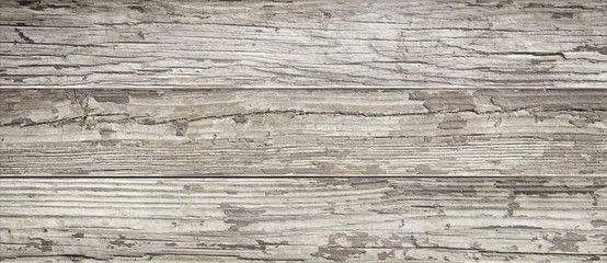 Aged wooden background of weathered distressed rustic wood boards with faded paint showing brown woodgrain texture