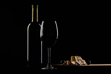 wine glass and bottle, cheese with mold  and grapes on black background