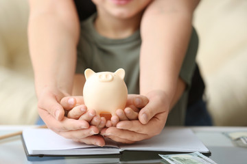 Mother and her little son holding piggy bank, closeup