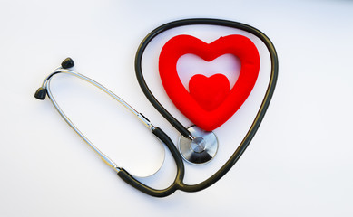 A stethoscope shaping a heart and a red heart over white background,