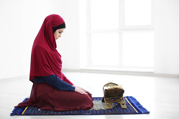 Young Muslim woman reading Koran, indoors