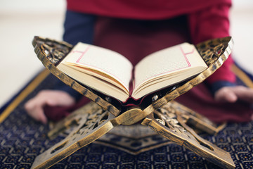 Muslim woman reading Koran, indoors
