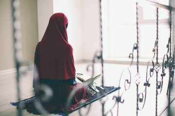 Young Muslim woman praying, indoors