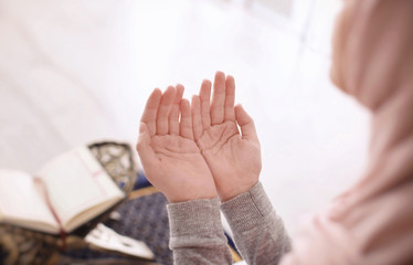 Young Muslim woman praying, indoors. Focus on hands