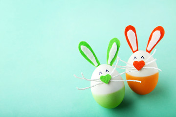 Eggs with funny rabbit faces on mint background