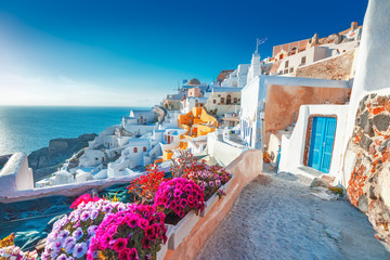 Fotobehang Santorini Santorini, Greece. Picturesq view of traditional cycladic Santorini houses on small street with flowers in foreground. Location: Oia village, Santorini, Greece. Vacations background.