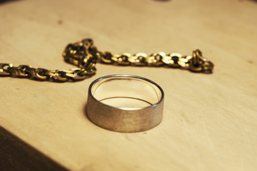 silver bracelet with gold snap hook c with diamonds, rings with stones lie on a textured tree.