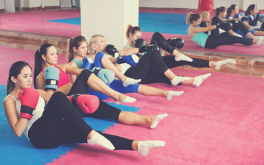 Group of female are doing exercise sitting