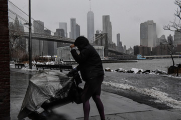 A person walks in the wind during a storm past the Manhattan skyline in the Brooklyn borough of New York City