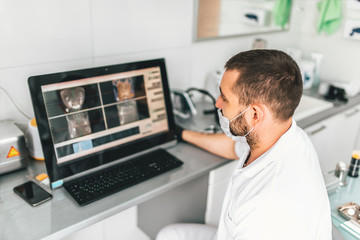 Doctor making examination of the x-ray and choosing treatment in the dental clinic