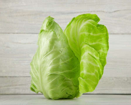 fresh green pointed cabbage on white wooden kitchen plate, can be used as background