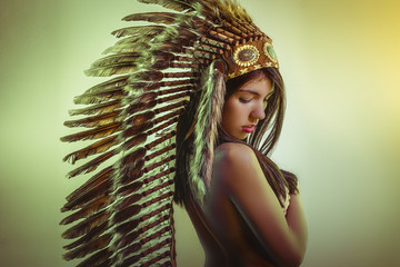 Ethnic Beautiful young brunette with big American Indian plume of brown feathers. has long black hair