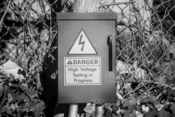An electrical fuse box with a danger warning