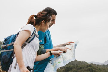 a couple with an asian girl and white guy looking for the way on a paper map