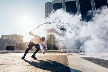 Man doing flip and holding smoke grenade in city